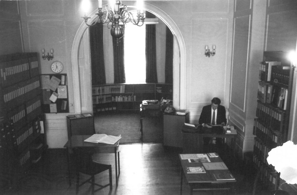 Black and White photograph of room with someone working at a desk